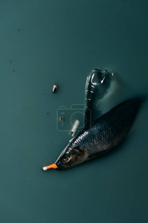 top view of fish, plastic bottle and cigarettes flowing in water, environmental protection concept