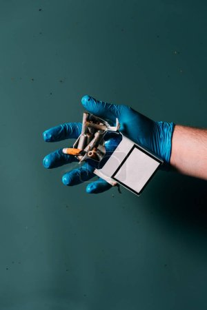 partial view of man in latex glove holding cigarettes in hand, ecosystem protection concept