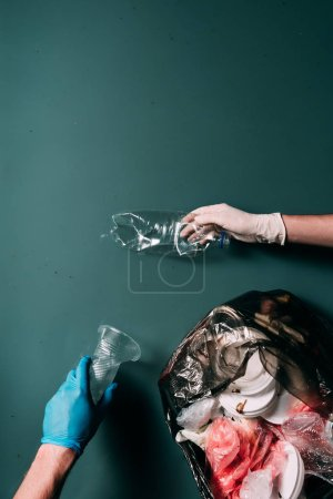 Photo for Cropped shot of man and woman in latex gloves cleaning water from garbage, ecology protection concept - Royalty Free Image