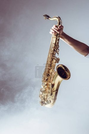 hand on young musician holding saxophone in smoke on grey