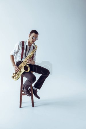 handsome young jazzman sitting on stool and playing saxophone on grey