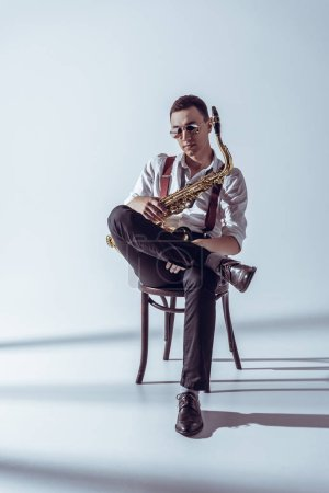 stylish young performer in sunglasses sitting on chair and holding saxophone on grey
