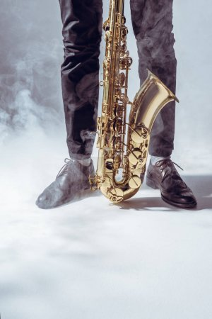 partial view of young musician standing with saxophone in smoke on grey