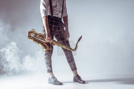 cropped shot of stylish young musician standing with saxophone in smoke on grey