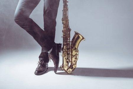 low section of professional musician standing with saxophone in smoke on grey