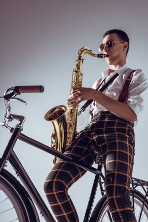 low angle view of young performer sitting on bicycle and playing saxophone on grey