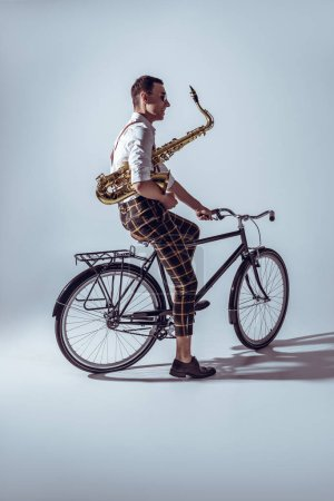 young stylish musician in sunglasses holding saxophone and riding bicycle on grey