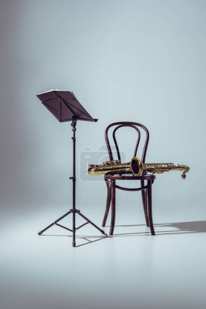 music stand for notes and professional saxophone on chair on grey