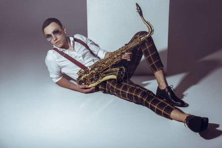handsome stylish young musician in sunglasses lying with saxophone on grey