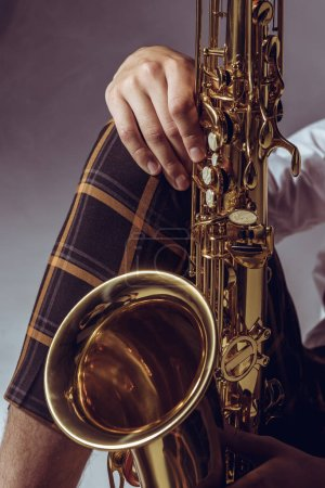 close-up partial view of stylish professional musician holding saxophone on grey