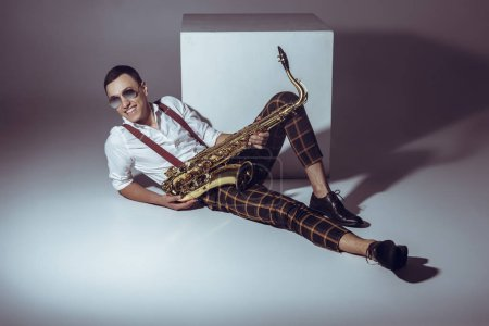 smiling young musician in sunglasses holding saxophone while lying on grey