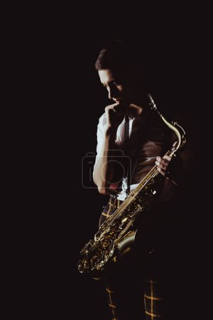 pensive young musician holding saxophone isolated on black