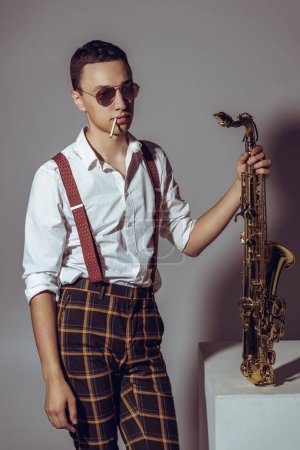 stylish young musician with cigarette holding saxophone on grey