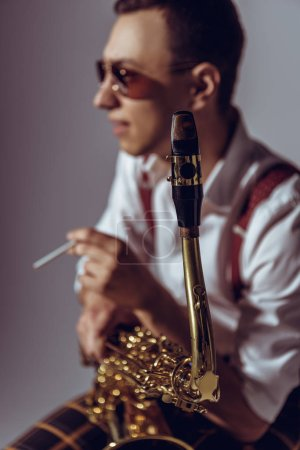 selective focus of young saxophonist smoking cigarette on grey