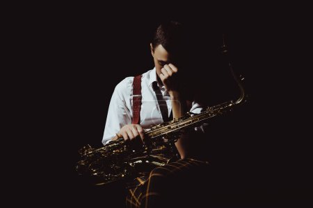 Photo for Young musician holding saxophone isolated on black - Royalty Free Image