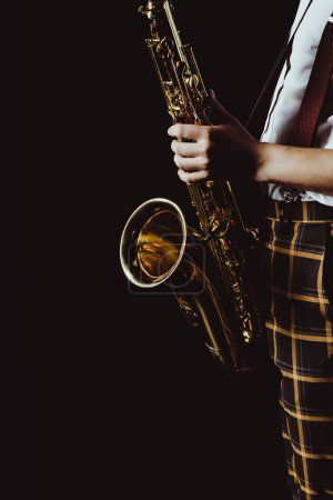 Photo pour Plan recadré de jeune musicien élégant tenant saxophone isolé sur noir - image libre de droit