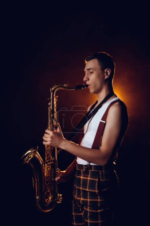 side view of professional stylish young jazzman playing saxophone