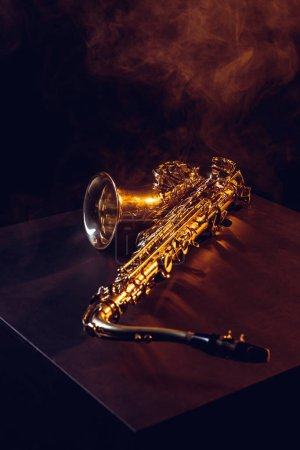 professional shiny saxophone in smoke and backlit on black