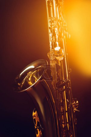 close-up view of shiny professional saxophone and spotlight on black