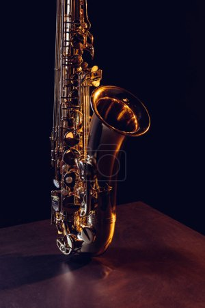 close-up view of shiny professional saxophone on black