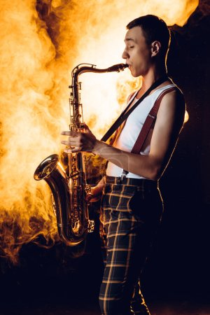 side view of expressive professional saxophonist playing sax in smoke
