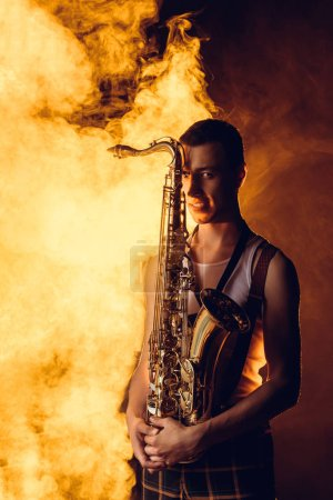 handsome stylish young musician holding saxophone and looking at camera in smoke