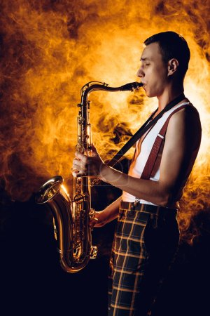 side view of expressive stylish young musician playing saxophone in smoke