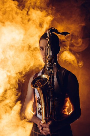 young male musician holding saxophone and looking at camera in smoke