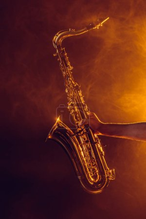 close-up partial view of young musician holding saxophone in smoke