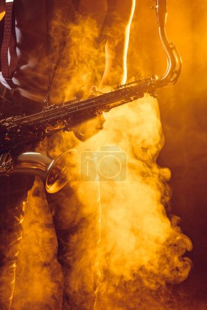 cropped shot of young musician holding saxophone in smoke