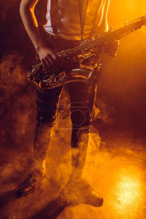 low section of young musician holding saxophone in smoke