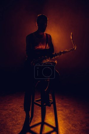 silhouette of young saxophonist sitting on stool with sax