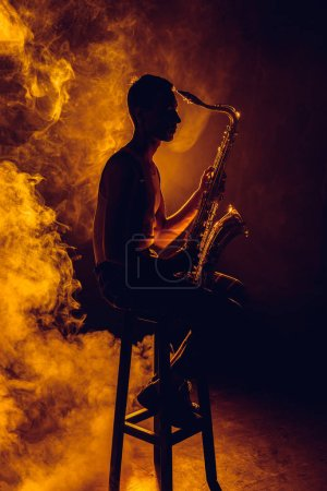 Photo for Side view of young musician sitting on stool and holding saxophone in smoke - Royalty Free Image