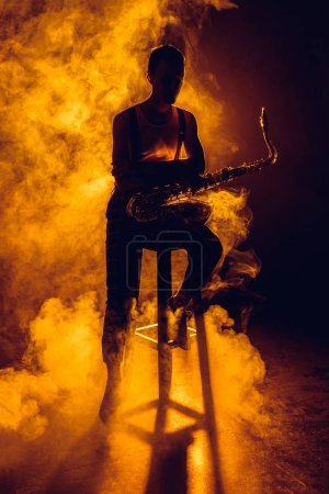 Photo for Silhouette of young musician sitting on stool and holding saxophone in smoke - Royalty Free Image
