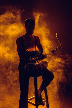 silhouette of young jazzman sitting on stool and holding saxophone in smoke