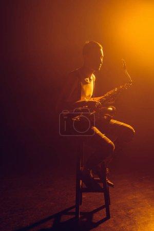 young stylish jazzman sitting on stool and holding saxophone
