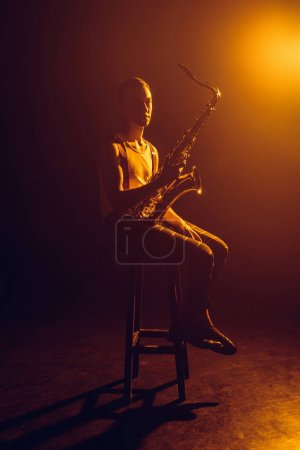 young jazzman looking at camera while sitting on stool and holding saxophone