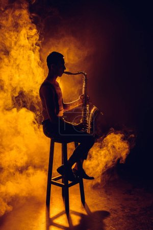 Photo for Silhouette of young musician sitting on stool and playing saxophone in smoke - Royalty Free Image