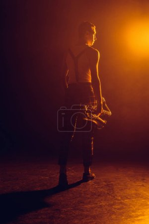 back view of young jazzman holding saxophone and looking away