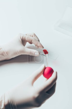 cropped shot of doctor pouring blood from pipette onto blood slide