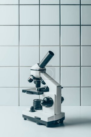 optical microscope on white tablet in front of tiled wall