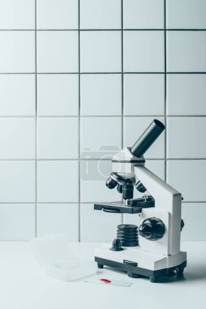 blood sample and optical microscope on white tablet in front of tiled wall