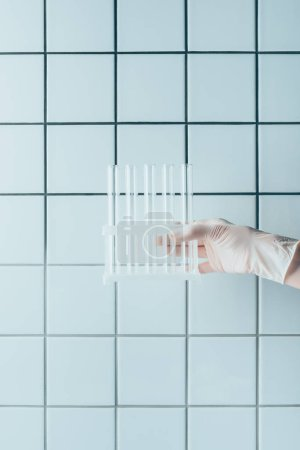 cropped shot of doctor in glove holding test tubes in stand in front of tiled white wall