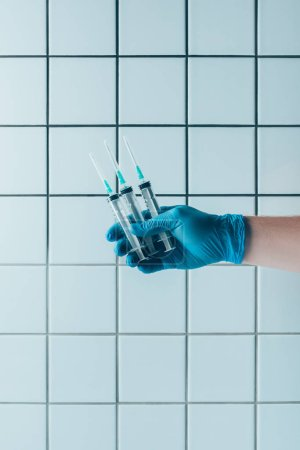 cropped shot of doctor in glove holding syringes in front of tiled white wall