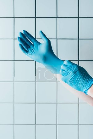 cropped shot of doctor putting on blue rubber gloves in front of tiled white wall
