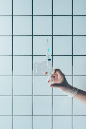 cropped shot of doctor in glove holding syringe with transparent liquid in front of tiled white wall