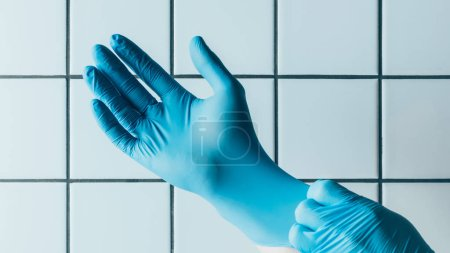 cropped shot of medical worker putting on blue rubber gloves in front of tiled white wall
