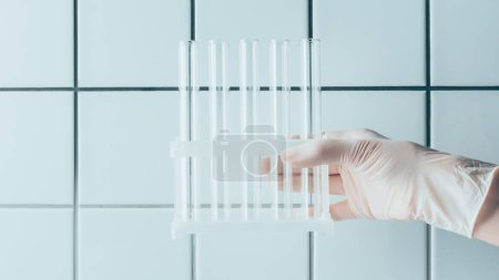 cropped shot of doctor holding test tubes in stand in front of tiled white wall
