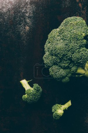top view of ripe broccoli on grey dark table