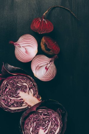 elevated view of halves of beetroot, onion and red cabbage on grey dark table